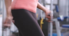 Young woman jumping rope at a gym, handheld panning shot Stock Footage