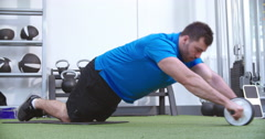 Man working out with an ab roller at a gym Stock Footage