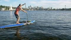Seattle,WA -Man on Lake Union Paddle Boarding with CIty Backgrou Stock Footage