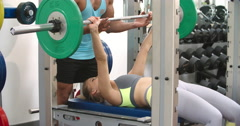 Young woman chest pressing barbells with a trainer at a gym - stock footage