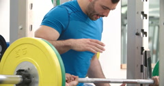 Trainer assisting man bench pressing barbells at a gym - stock footage