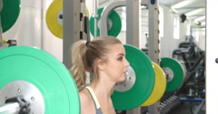 Young woman squat lifting weights at a gym Arkistovideo