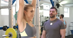Trainer advising a woman exercising with dumbbells at a gym Stock Footage