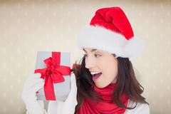 Composite image of astonished brunette in santa hat showing gift - stock photo