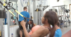 Young woman training with resistance straps in a busy gym Stock Footage