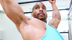 Muscular young man exercising on monkey bars at a gym Stock Footage
