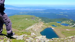 Hiker Man admires a beautiful view from mountain top peak in Bulgaria Stock Footage
