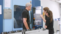 Two Apprentices Working With Engineer On CNC Machinery Stock Footage
