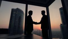 Two businessmen partners handshake in office. Silhouettes at sunset outside Stock Footage