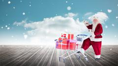 Stock Photo of Composite image of santa delivering gifts from cart