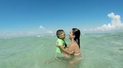 Woman and child playing in the ocean, shot also from under the water Stock Footage
