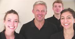Smiling decorating team, handheld, slow motion panning shot - stock footage