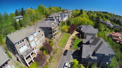 Stock Video Footage of An aerial image over a typical american suburban street and condos with a car