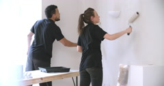Two people from a decorating team painting wall with rollers Stock Footage