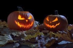 Creepy two pumpkins as jack o lantern among dried leaves on black background Kuvituskuvat