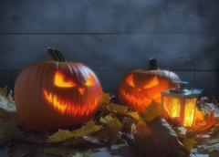 Spooky pumpkins jack o lantern among dried leaves on wooden fence - stock photo