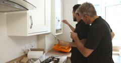 Engineer teaching apprentice how to program domestic boiler - stock footage