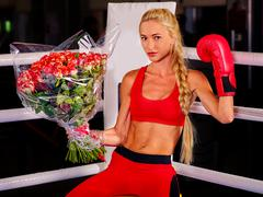 Girl wearing red gloves sitting in corner of boxing ring - stock photo