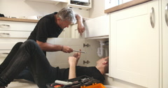 Stock Video Footage of Plumber teaching apprentice to fix kitchen sink