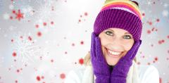 Stock Photo of Composite image of radiant young woman with cap and gloves in the winter