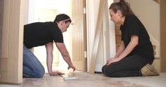 Man and woman laying laminate wood panel flooring in a house Stock Footage