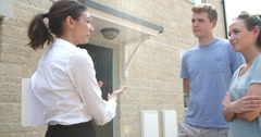 Young couple viewing a house with female real estate agent - stock footage