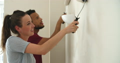 Young couple decorating home with paint rollers, close up Stock Footage