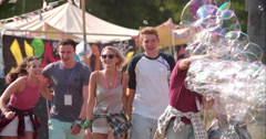 Friends walk through bubbles at music festival, slow motion Stock Footage