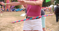 Girl hula-hooping at a music festival, slow motion Stock Footage