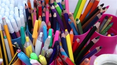 Color pencils and pens in plastic cups Stock Footage