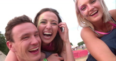 Young friends piggy backing at a music festival, close-up Stock Footage