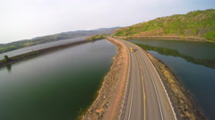 An aerial shot of cars on a highway crossing a lake or reservoir. Stock Footage