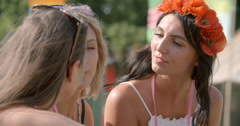 Three girlfriends talking at a music festival, close-up Stock Footage