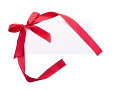 Card note with red ribbon on white background - stock photo