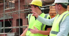 Stock Video Footage of Builder On Building Site Discussing Work With Apprentice