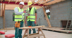 Carpenter With Male Apprentice Measuring And Cutting Wood Stock Footage