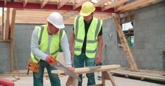 Carpenter With Male Apprentice Cutting Wood On Building Site Stock Footage