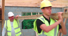 Stock Video Footage of Builder And Apprentice Carrying Wood On Construction Site