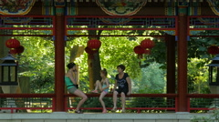 Tourists resting in a pagoda pavilion at Chinese garden in Lazienki Park, Warsaw Stock Footage