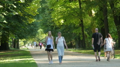 Two young women and other tourists walking in Lazienki Park, Warsaw Stock Footage
