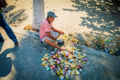 Man recycling empty cans in the street, Colombia Stock Photos