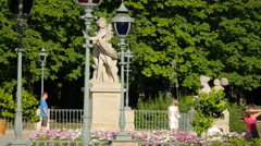 Tourists passing by Hermaphroditus and Salmacis statue in Lazienki Park, Warsaw Stock Footage