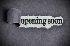 Opening soon word under torn black sugar paper Stock Photos