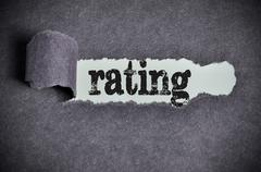 rating word under torn black sugar paper - stock photo