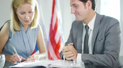 4K Male & female diplomats in office sign an agreement & shake hands on the deal - stock footage
