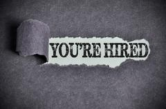 you're hired word under torn black sugar paper - stock photo