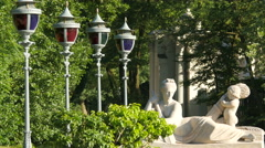 Street lights with colored glass and a statue in Lazienki Park, Warsaw Stock Footage