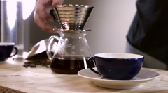 Barista pours hand brew coffee into a conventional cup Stock Footage