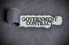 government contract word under torn black sugar paper - stock photo