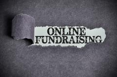 online fundraising word under torn black sugar paper - stock photo